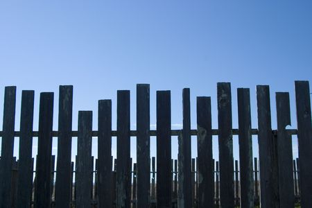 A line of dark wooden fence posts. Stock Photo