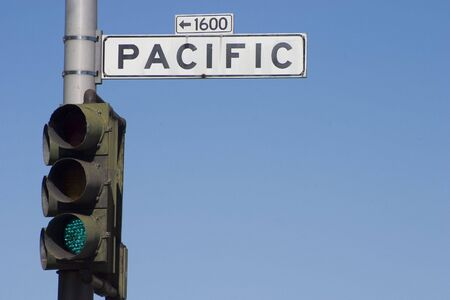 """A street lamp with the green light on, with a """"Pacific"""" road sign attached. Reklamní fotografie"""