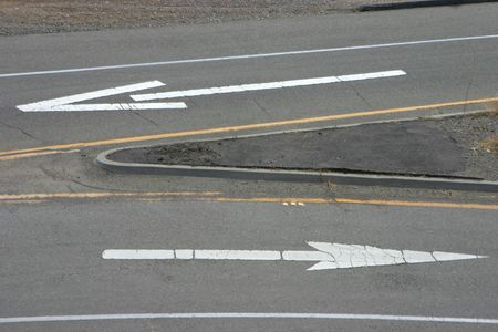choose a path: Painted road arrows pointing in the opposite direction.