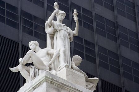 neocl�sico: Una estatua de una mujer con dos llamas en la parte superior de un edificio de estilo neocl�sico.
