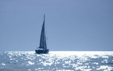 A sailboat cruises in the sparkling waters of sunset. Banco de Imagens