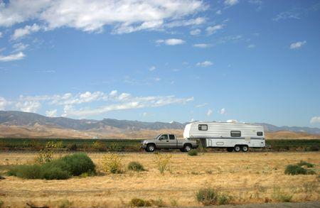 A truck pulls along a motor-home trailer.