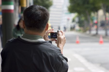 A tourist shoots some video of a city street.