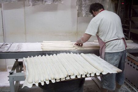 A French baker prepares the morning baguettes.