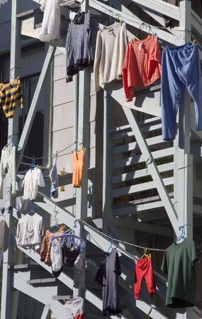 Clothes hanging out to dry on the side of a city apartment.