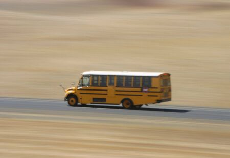 A motion-blurred school bus rips along the road.