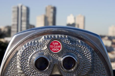A set of tourist binoculars looks towards a dense part of San Francisco.