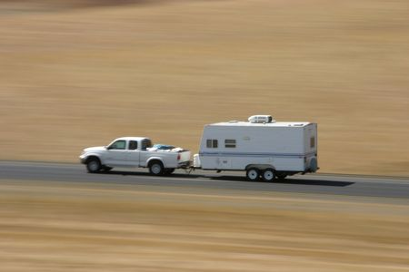 A pickup truck hauls a family camping trailer along the road.
