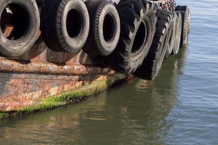 I vecchi pneumatici servono da paraurti per un rimorchiatore. Archivio Fotografico - 404627
