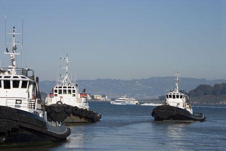 shove: A group of tugboats chug along in San Francisco bay. Stock Photo