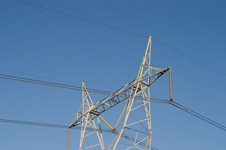 High voltage lines are held aloft by a giant power tower. 版權商用圖片