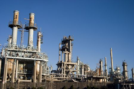 The complex arrangement of metal pipes and smoke stacks of a modern oil refinery. Banco de Imagens