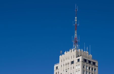The top of a tall apartment building with a radio broadcast antenna.