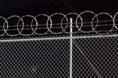 concertina: Razor wire spirals against the dark interior of a warehouse.