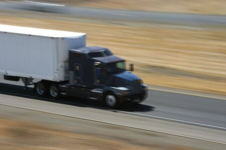 A tractor-trailer hauls some stuff down the highway. Stock Photo - 416497