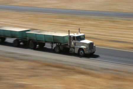 A tractor-trailer hauls some stuff down the highway. Stock Photo - 416500