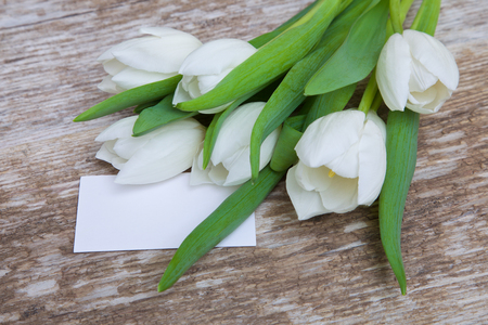 wood panel: white tulips bouquet and blank greeting card