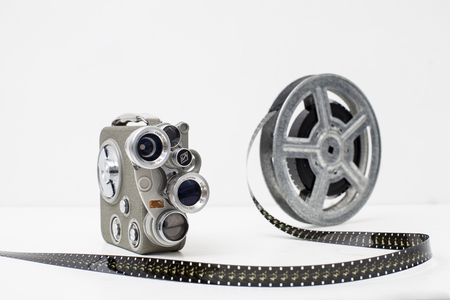 old movie camera with film reel on white background