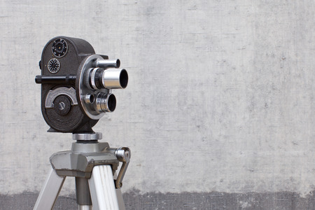 Old movie camera on painted background