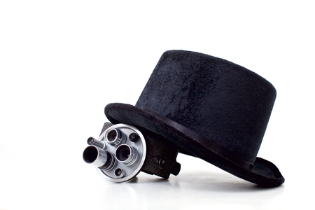 old film camera and black hat on white