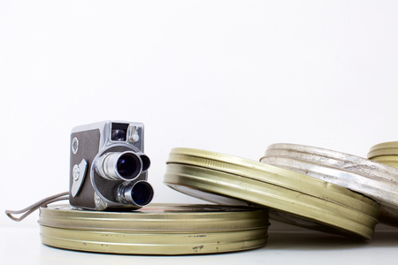 Old movie camera and film canisters on white Stock Photo