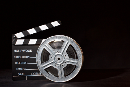 Clapperboard and film reel on the black background