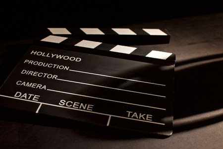 movie clapper with shadow on wooden black background