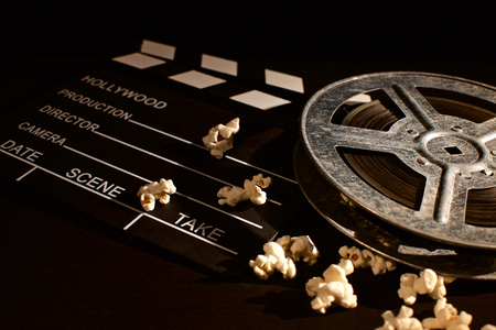 Movie clapper board with popcorn on the wooden table