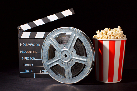 movie film reel and film clapper with popcorn box on black Stock Photo
