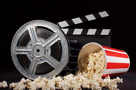 movie film reel and film clapper with popcorn box on black Reklamní fotografie