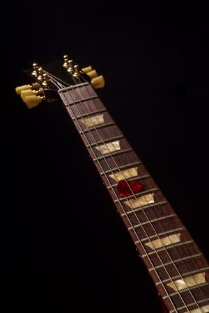 red guitar pick on the fingerboard and dark Reklamní fotografie