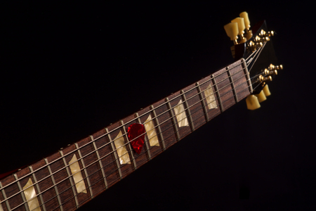 red guitar pick on the fingerboard and dark Archivio Fotografico