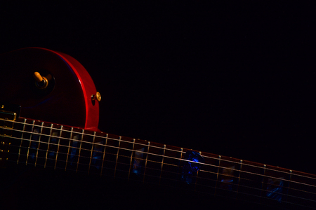 blue guitar pick on the fingerboard and dark Banque d'images