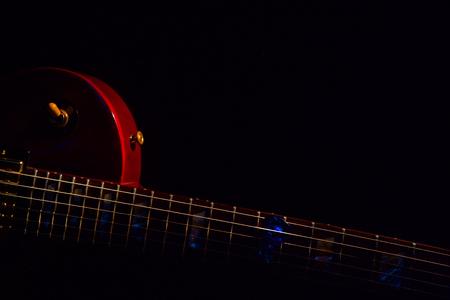 blue guitar pick on the fingerboard and dark Reklamní fotografie