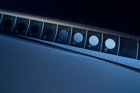 Old film strip with blue shadow on dark