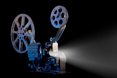 movie projector with film reels on black background