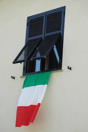 a window on the world: An Italian flag hangs from a window after Italy won the world cup summer 2006. Stock Photo
