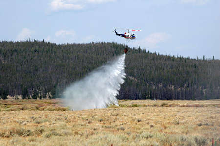 A helicopter attempting to dump water on a nearby forest fire, loses its load early, forcing it to refill in a nearby river. photo