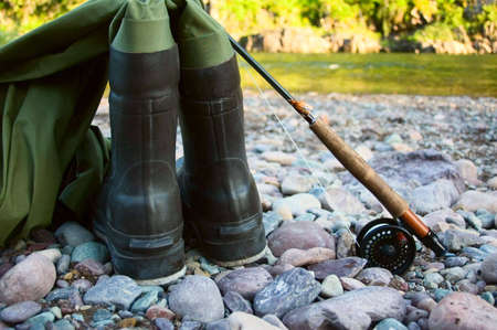 waders: A pair of waders sit along a river bed with a fishing rod and reel, ready to be used for flyfishing.