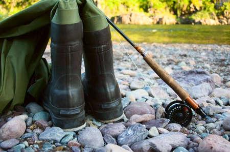 waders: Un par de botas sentarse a lo largo de un cauce con una ca�a de pescar y carrete, listo para ser utilizado para pesca con mosca.