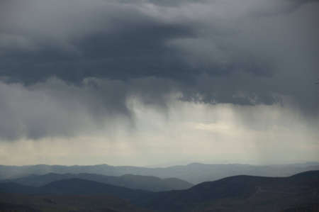 gather: Storm clouds gather over the Rocky Mountains. Stock Photo