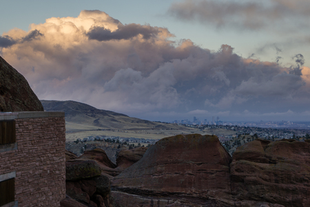 A big cloud sits over Denver during sunset, viewed from nearby Morrison, Colorado.