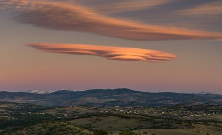 lenticular: Sunrise in Colorado, with a massive lenticular cloud over the rocky mountains.