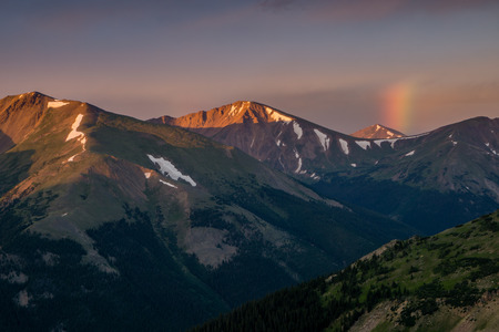 A small rainbow makes an appearance during the sunrise from Vasquez Peak, in Colorado. Stock Photo
