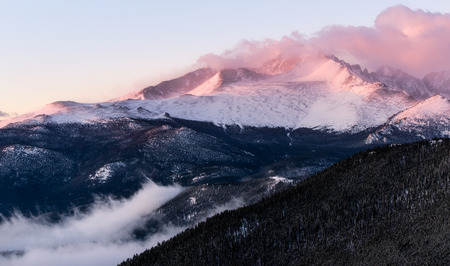 A foggy morning in Rocky Mountain National Park.  A lovely view of the alpen glow on Longs Peak.  Estes Park, Colorado.