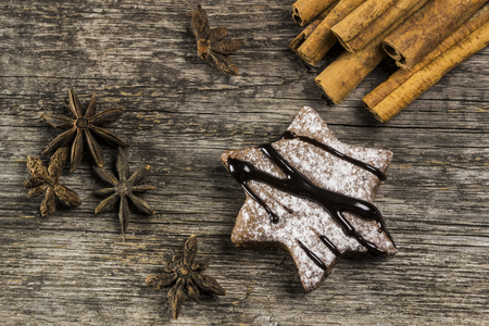 Ginger biscuits with chocolate cream on a wooden background, cinnamon