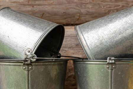 Stack of vintage metal buckets on a market stall, with enamel paint and wooden handles