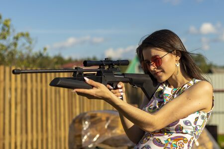 Pretty hunter girl aiming with hunting rifle in the outer wood. Carbine with optical-sight.