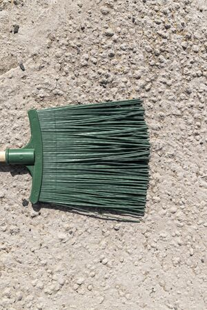 Close up of green broom brushing grey crumbled concrete sidewalk outdoors, cleaning