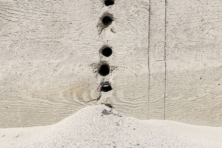 Cracks holes on the cement wall Caused by drilling To put the plumbing tube in the house